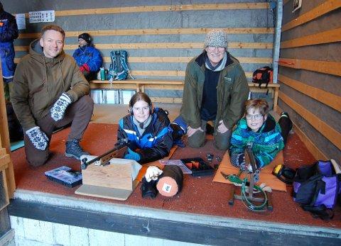 UNGE OG IVRIGE SKYTTERE: Søskenene Johanne (13) og Erik (11) Idland er ivrige medlemmer av Ski skytterlag. her ligger de på standplassen på Granrud skytebane under oppsyn av lagets leder, Gard Heiaas (t.v.) og mangeårige tidligere leder Ivar Liseter, som har skrevet lagets 150-års historie.