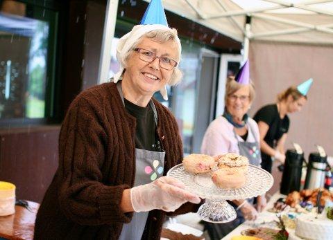 SMILENDE SERVITØR: Pensjonist Aud Sørli stiller frivillig opp og hjelper til med serveringen ved kakebordet.