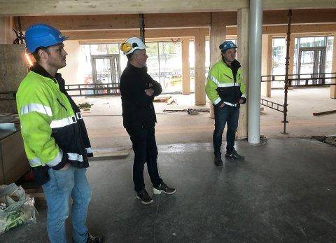 Prosjekteringsleder Jørn Sindre Flyum (til venstre) og prosjektleder Svein Inge Kvande (til høyre) fra Consto Surnadal, og Olav Rønning fra Surnadal kommune på befaring på nye Surnadal barne- og ungdomsskule. Her står de i det gamle inngangspartiet, og bak de tre herrene ser vi den nye kantinen i et påbygg mot nord. Fotografen står med ryggen til dagens kantine, som nå skal bli bibliotek.