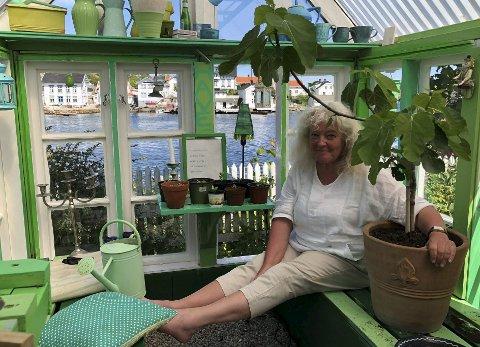 Vakre omgivelser: Anne-Line Henriksen er veldig glad i drivhuset ektemannen Terje har laget til henne. Her kan de ofte sitte med et glass. Fikentreet overlevde vinteren, og får masse kjærlighet av Anne-Line. Hun tror på å snakke med blomstene, og «lille fiken» er intet unntak. Fra drivhuset er det utsikt over til Holmen. Til Holmen kom Anne-Line flyttende fra Frankrike da hun var åtte år gammel. Siden har hun blitt i Lyngør.  Foto: Siri Fossing