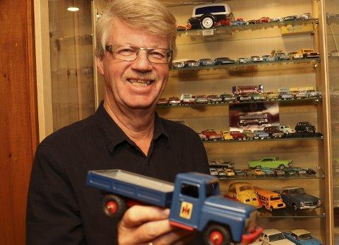 SAMLER PÅ MODELLER: Eric Lunde har mange biler i glasskap på hobbyrommet. Her holder han fram en International lastebil.