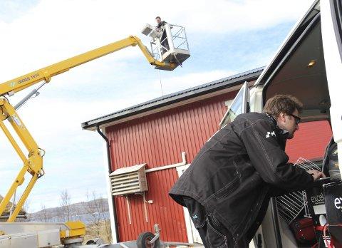 NY KUNDE: Cosinus AS monterer antenne på Angarsneset i Leirfjord. I liften står Kristoffer Martinsen mens Steinar Pedersen sjekker signalene på bakken.Foto: Jarl G. Sandholm
