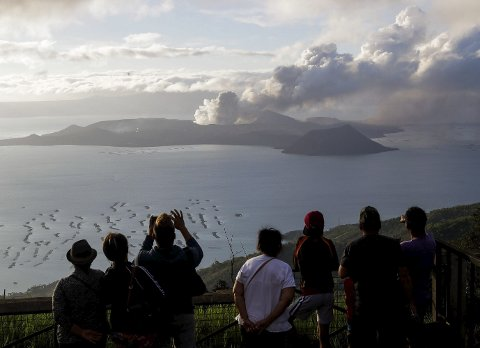 ASKE: Folk frå Tagaytay i provinsen Cavite sør for Manila står og ser på medan vulkanen Taal held fram med å spy ut aske tysdag 14. januar. (Foto: Scanpix/Aaron Favila).