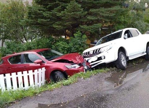 KRAFTIG SMELL: Den røde bilens to parkert lagne veien, og skal ble skjøvet flere meter før begge bilene havnet i en hage.