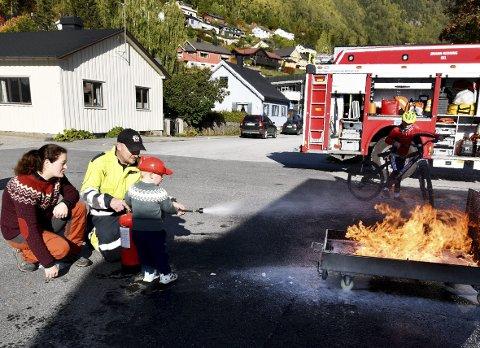 Fikk prøve: Emil Moen prøver å slukke brann med skumapparat, med god hjelp av Harald Aasheim i Sel brann- og redningsvesen. Mor June Moen ser på.