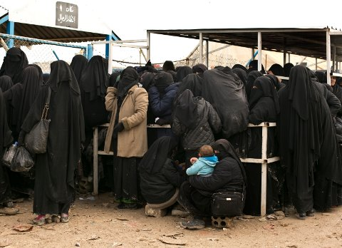 FILE - In this March 31, 2019 file photo, women residents from former Islamic State-held areas in Syria line up for aid supplies at Al-Hol camp in Hassakeh province, Syria. The leader of the Islamic State group released a new alleged audio recording Monday, Sept. 16, 2019, calling on members of the extremist group to do all they can to free IS detainees and women held in jails and camps. (AP Photo/Maya Alleruzzo, File)