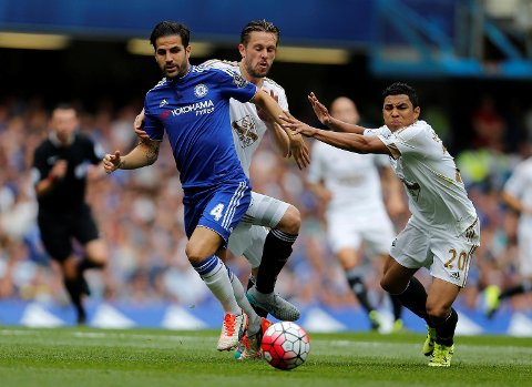 Chelsea's Cesc Fabregas, left, and Swansea's Gylfi Sigurosson and Jefferson Montero, right, challenge for the ball during the English Premier League soccer match between Chelsea and Swansea City at Stamford Bridge stadium in London, Saturday, Aug. 8, 2015.(AP Photo/Frank Augstein)