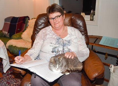 DIKT: Jorun Johannessen Tandberg passer på å ha en notatbok i nærheten så hun får skrevet ned diktene som dukker opp. Katten Minnie legger seg gjerne oppå boken for litt kos de gangene hun skriver.