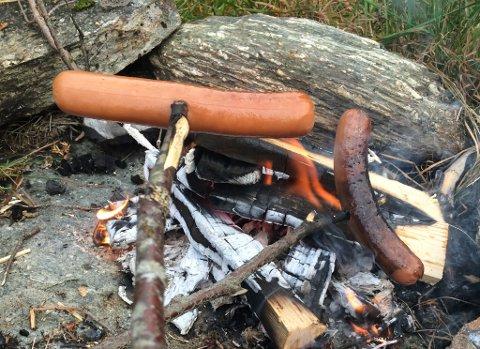 Det er fristande å grille pølser på bål når det er så flott vêr, men pass på at du har vatn å sløkke med, skulle det gå gale.