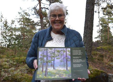 Spent: Lillian Sandmo Camfield med sitt eget maleri «Solgløtt», som er ett av syv kunstverk som nå skal henge oppe på turstier i Grååsen, Griniskogen og i Sansehagen ved Grinitun.