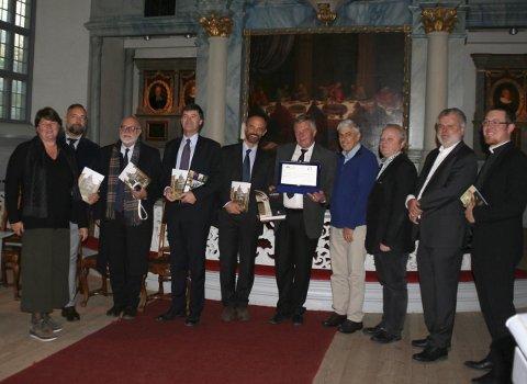 FORFATTERE SOM TREKKPLASTER: Den italienske delegasjonen og Røros kommunes representanter valgte Røros kirke for å markere at et samarbeid om å markedsføre hverandre som litterære landskap er på trappene.