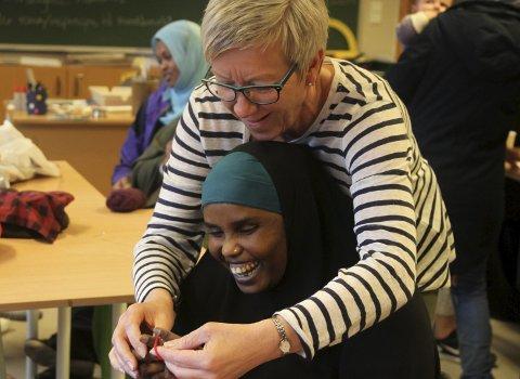 1. intrikat: Mette lærer Kalud frå Somalia å strikke. Det er ikkje berre-berre å stokke fingar, pinnar og garn til å byrje med! 2. konsentrasjon: Lang lang rekke med damer som har fullt fokus på saumen. 3. moro må vi ha: Maranata har fått ferdig kjolen sin, og det er ingen utveg for Mette - den må prøvast på! 4. lett som ein plett: 12 år gamle Noor frå Syria strikkar skjerf: – Det er kjempelett, seier ho nøgd, – når eg er ferdig skal eg strikke lue.alle foto: liv standal