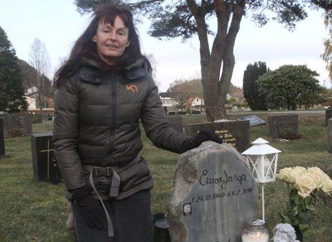 VISER MEIR: Herdis Seim ved mannen Einar Lunga sin gravstein – som ho fann i Botnane. Til venstre på steinen er den vesle brikka som inneheld bilde, musikk og film om Einar.