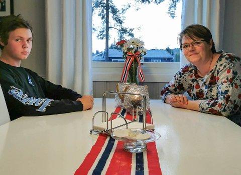 17. MAI MED KARANTENE: Oliver Bjørnerud, og 90 medelever, måtte holde seg hjemme på nasjonaldagen. Mamma Marit har sluppet ut av ventekarantene, og forsøker å holde humøret oppe på 17. mai. – Men det blir omtrent som en vanlig hverdag i år.