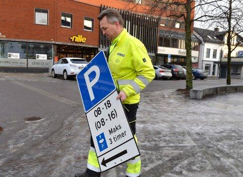 SKRUR: Frode Eriksen, fagarbeider fra vei og trafikk hengte fredag formiddag opp skiltene. Nå er det gratis parkering i tre timer på Aagaards plass.