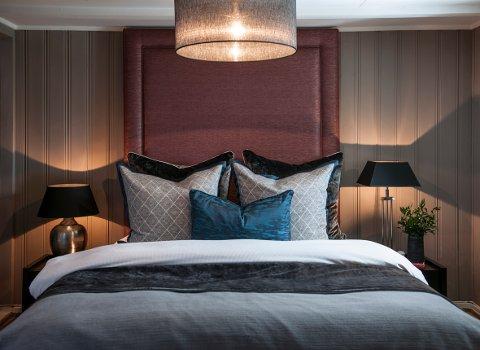 Med mørke farger, stemningsbelysning, eksklusive tekstiler med ulik tekstur og polstret sengegavl helt opp til taket, skal det mye til for ikke å kjenne hverdagsluksusen.