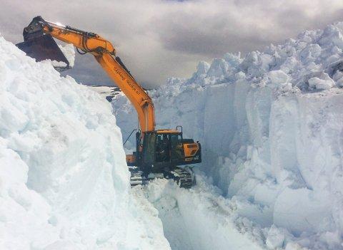 Mannskap frå BBK held på å fjerne store mengder med tettpakka snø frå flaumløpet til Skjerjavatnet i Vestland. Foto: BKK / NTB scanpix