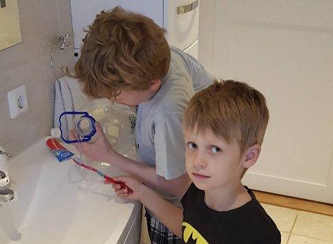 Drikkevann må kokes, og her hjelper Sakarias (11) lillebroren Georg (6) med å fylle i vann fra flaske.