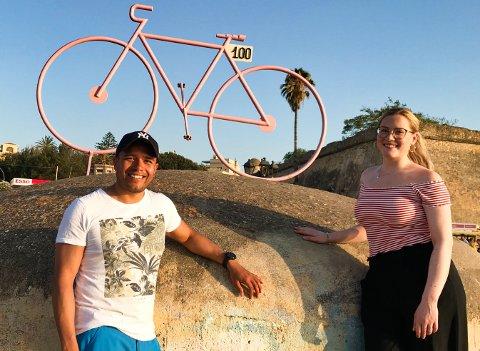 STARTER SYKKELSKOLE: Christian M. Sæther og forloveden Amanda Nordstrand, her på sykkelferie i italienske Alghero på Sardinia. I bakgrunnen er en rosa sykkel som ble satt opp i forbindelse sykkelrittet Giro d'Italias 100. utgave i 2017.