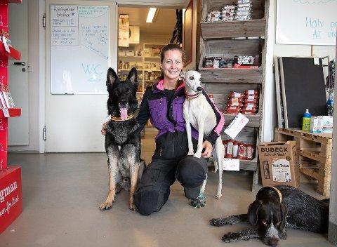 ØNSKER VELKOMMEN FOR HANDEL: Natalie Nielsen er butikkansvarlig. Hun har tre gode venner og treningskamerater  Zlatan ( Schäferhund), Elle (Wippet) og  Hufta  (strihåret vorsterhund).