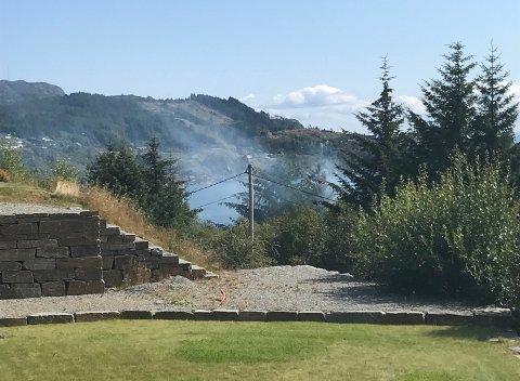 Evakuerte beboere ser røyken i det fjerne.