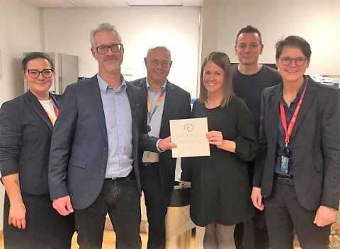 JULEGAVE: Fredrik Hellström og Eline Udnesseter har et solid grep om hver sin side av sjekken fra Sparebankstiftelsen. Mellom de to, står Kjell Bjønnes, regional banksjef for privatmarkedet i DnB.