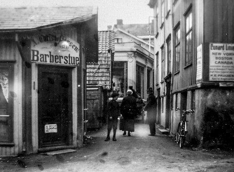 Ved Jens Lauersøns plass 1916: Dette er Kragerø for 100 år siden. Bildet ble tatt i jubileumsåret 1916, da Kragerø var 250 år. Stredet er Jens Lauersøns plass, hvor plassen på den tiden var begrenset. Tre av disse husene eksisterer ikke i dag. Til venstre sees Kragerøs største frisør- og barbersalong A. Christoffersen. Huset til høyre er Kringsjågården, som ble revet midt på 1960-tallet. Bildet viser til fulle hvor trange Kragerøs gater var tidligere. Midt i bildet kan man se en mann med hest og vogn.