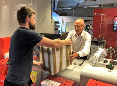 ØKT NETTHANDEL: Gjøvik postkontor utvider åpningstiden for å kunne ta seg av økt netthandel. Her er det Kevin Dalby fra Gjøvik som skal sende en drone han har solgt på nett. Daglig leder ved postkontoret, Odd Tveit, hjelper ham.