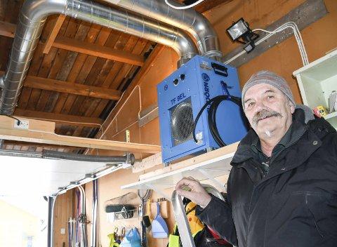 Varmer opp: Odd Erik Opland har funnet opp en egen løsning der han varmer opp taket for at snøen skal skli av. – Det tar bare 5 til 15 minutter fra jeg setter på varmeviften til snøen er borte fra taket. Som bildet viser går det tykke rør som slipper varme inn mellom taklagene. Foto: Gøran O. Pedersen