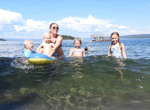BØLGER: Kristine Krey Holmstad med badeglade barn idet danskebåtbølgene kommer inn.