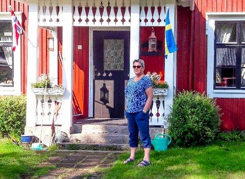 Både det svenske og norske flagget pryder inngangen til den rødmalte idyllen til Brit Homstvedt (72) fra Havnås. Her tilbringer hun og mannen mye tid gjennom alle årstider – og gjerne sammen med barn, barnebarn og oldebarn.