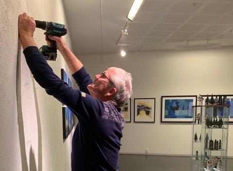 Olav Karlstad- Surnadal kunstforenings dyktige handyman monterer de siste bildene før åpningen lørdag.