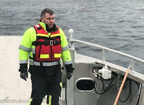 Driftsleiar Ørjan Storesund i Flora Hamn er ute og plukkar opp ei lita jolle på rek. Du ser såvidt i båten til høgre for Storesund på bildet.