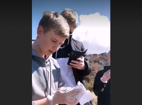 UNDERSØKER: David Alsaker leser opp meldingen de fant i strandkanten.
