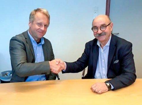 I BOKS: Trøgstad kommunes ordfører Saxe Frøshaug (t.v.) og Bernt Otto Follestad i Viken Fiber gir hverandre håndslaget på Trøgstad-avtalen. Fiberutbyggingen skal skje i løpet av 2019. FOTO: Viken Fiber