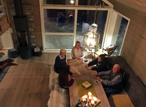 MODERNE: En aldrende hytte og et nytt byggesett er blitt til en moderne hytte med aner fra en svunnen tid. Ann-Iren Haugen (i midten) og familien nyter en kveld på hytta.