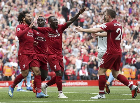 Liverpool's Mohamed Salah, left, celebrates scoring his side's first goal of the game during the Premier League soccer match between Liverpool and West Ham at Anfield, Liverpool, England. Sunday Aug. 12, 2018. (David Davies/PA via AP)