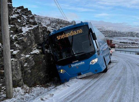 STÅR GODT: Bussen, som måtte kjøre av veien for ikke å kollidere, står helt inntil fjellveggen, og dermed måtte sjåføren klatre ut av vinduet. I bakgrunn skimtes også vogntoget som kom i møte.