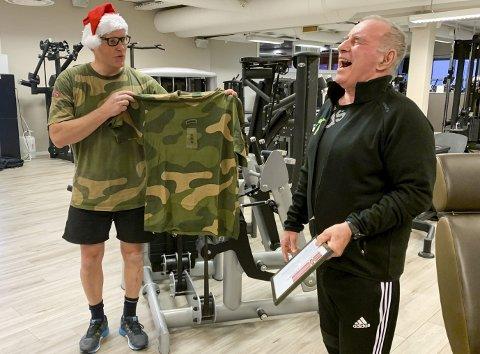 BESKIKKET PÅ 75-ÅRSDAGEN: – Siden du nå er blitt drillkaptein, må du ha tilhørende trenings-skjorte, sa Finn Gunnar Jacobsen (t.v.) da Jan Tore Henriksen ble overrasket på 75-årsdagen sin. FOTO: BJØRN TORE BRØSKE