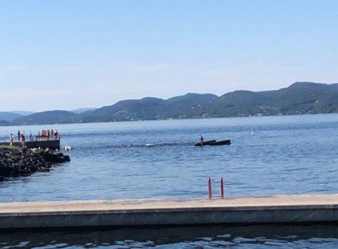 Her ligger flytebrygga opp ned i vannet. Personene som var oppå er på vei inn på land.