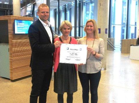 Her overrekker Tore Bjelland fra NIF Fotball og Marianne Ellingstad(t.h), styreleder i NIF, sjekken på 300.000 til ordfører Nina Sandberg, som skal være med på å finansiere to nye kunstgressbaner på Berger.