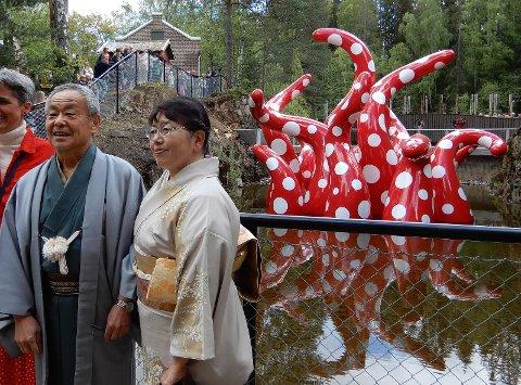 STO FOR AVDUKINGEN: Japans amassadør Masahiro Tauchi med følge foran den spesiallagde skulputuren av Kusama.