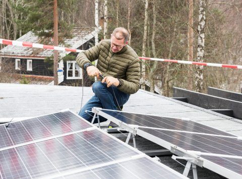 SOLSTRØM: Dag Heim følger med og hjelper litt til når de 20 solcellepanelene blir montert på taket.