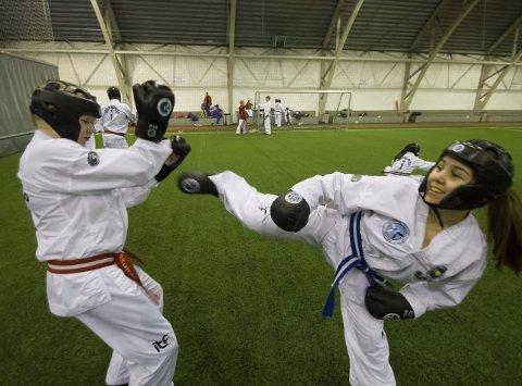 SOSIALISERING ER VIKTIGST: Sparring er gøy, men Julie Sundstrøm (13, til venstre) fra Kirkenes og Mathilde Andersson (15) fra Alta synes å møte andre tilhengere av taekwondo er det beste med fylkesmesterskapet. Foto: Stian Hansen