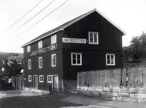 """BRØNNGATA. Tvers overfor hverandre i Brønngata lå disse to bedriftene, til venstre """"Larvik Mølle"""" som ble oppført etter at en eldre møllebygning hadde brent ned i 1903, og til høyre """"Larvik Traastiftfabrikk,"""" populært kalt """"Spikern"""". Mellom bygningen og plankegjerdet stikker Larviks korteste og trangeste gate inn: """"Brønnstredet,"""" eller på folkemunne: """"Trullen"""". Bildene fra ca 1910-15."""
