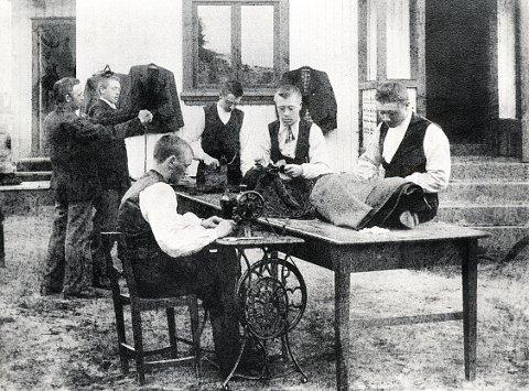 FOLDVIK. Fra Karl Anton Larsens skredderverksted på Vestre Foldvik omkring 1900. Larsen hadde flere svenner i arbeid. Noen av dem kom langveis fra og hadde kost og losji som en del av lønna. Merk de to som sitter på bordet i klassisk skredderstilling. Bygdeskredderen selv ses med målebåndet i bakgrunnen.
