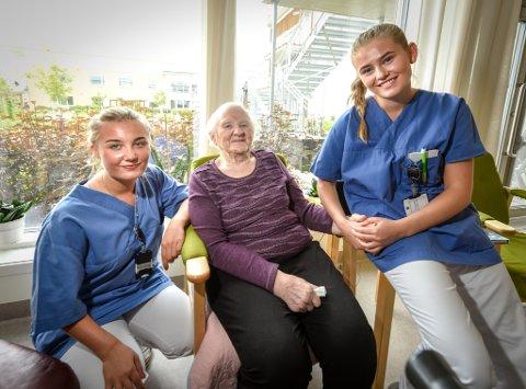 F.v. Liselotte Edvardsen (18)  og Maren Kvernberg Martiniussen (17), på hver sin side av Gunvor Snefjellå (93) trives godt i sommerjobben på Selfors sykehjem. Det beste med jobben, er beboerne.