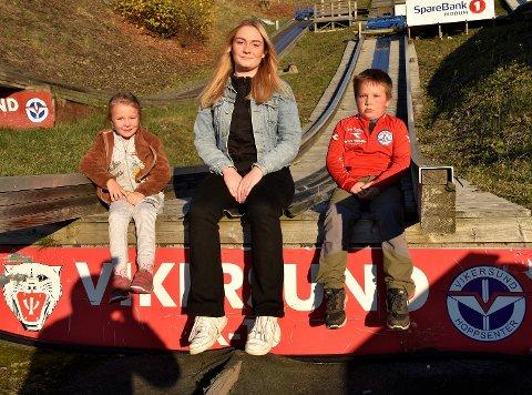 TRIVES SOM TRENER: Liv Grete Kiesling dingler med beina på hoppkanten, og venter på snøen -  sammen med to av sine elever. Hedvig Olava Hæhre (5) og Vebjørn Fredriksen (7).
