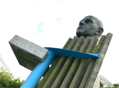 BENK: Noen har satt en av de tunge benkene i parken på siden. Benken lener seg over statuen av Gunnar Hellesen.