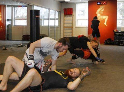 BRYTETRENING: Mixed martial arts, eller MMA som er det vanlige navnet, er en kampsport som tillater bruk av både slag- og grapplingteknikker, stående og på bakken. Eirik Arntsen lærer bort teknikker som først og fremst går på bryting, og kamp på bakken. Her er Jo og Halvard i kamp i forgrunnen og Eirik og Robert bak.  FOTO: PER VIKAN